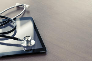 Studio macro of a stethoscope and digital tablet with shallow DOF evenly matched abstract on wood table background copy space