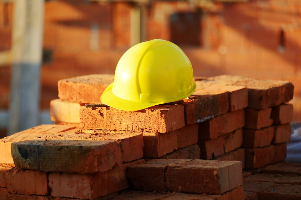 Under construction, helmet and bricks for building site